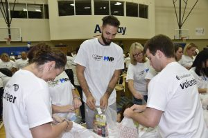 Orlando Magic staff members (including Magic player Evan Fournier) participate in a full staff food packing service project with employees from UnitedHealthcare.   Photos taken by Gary Bassing.