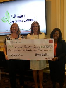 Anna Spencer of WEC receiving a $5,500 grant presented by Wells Fargo Principal Business Relationship Manager Valerie McDonald, a WEC council member and Daphne Zizi Wells Fargo Business Banking Intern.